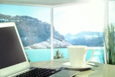 Laptop on vacation in front of water and mountains